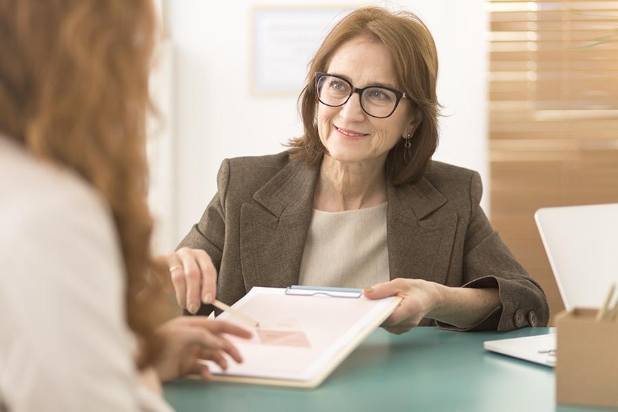Health Reimbursement Arrangement - Professional Advisor Working with Her Employee and Going Over Reimbursement Plans in the Office
