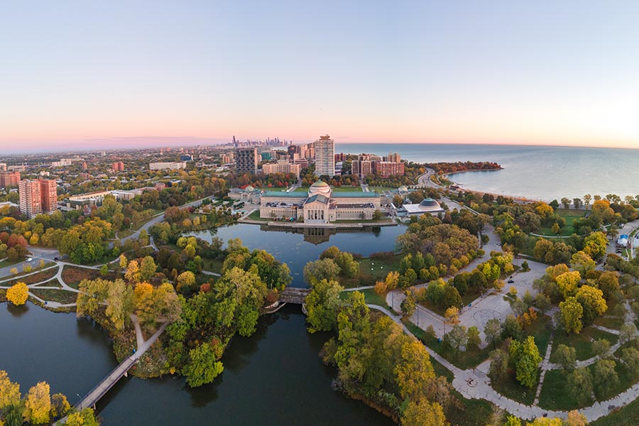 About Us - Aerial View of University Campus, Lakes, and Chicago Skyline at Dusk, the Trees Below Turning Colors in the Fall