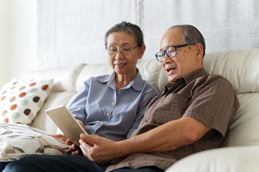 Blog - Senior Couple Uses a Tablet on Their White Leather Couch