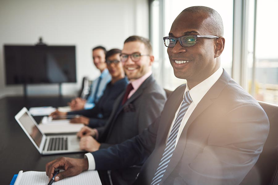 Employee Benefits - Employees at a Law Firm Smile at the Camera While Sitting at a Conference Table, Large Windows to Their Right