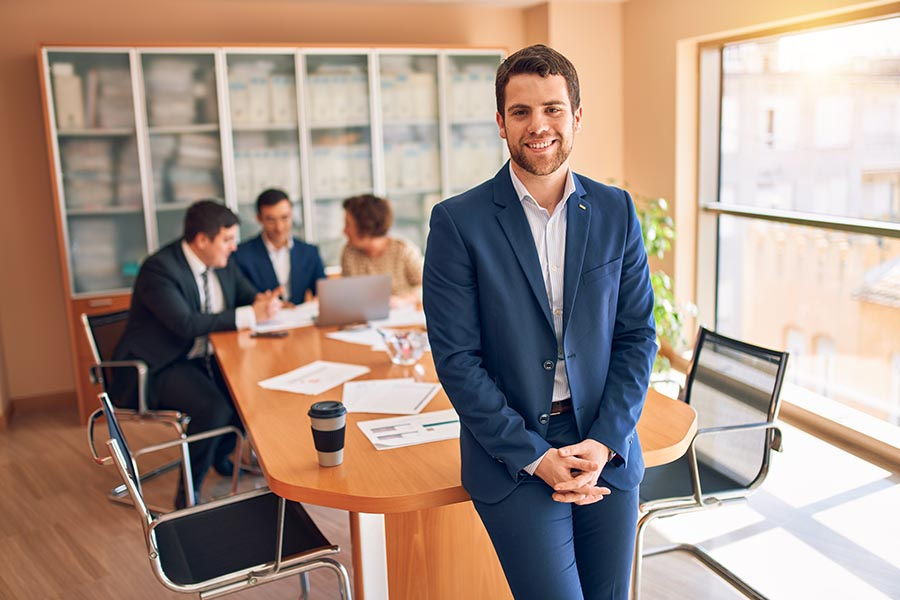 Business Insurance - Lawyer Perches on the Edge of a Conference Table as His Associates Collaborate Behind Him, a Large Bookshelf at One End of the Meeting Room